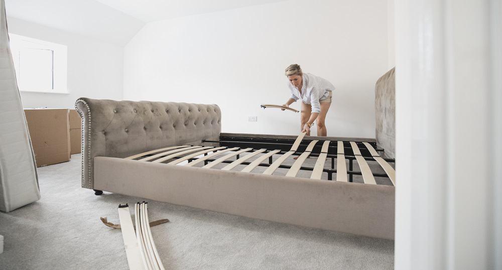 woman installing bed frame slats
